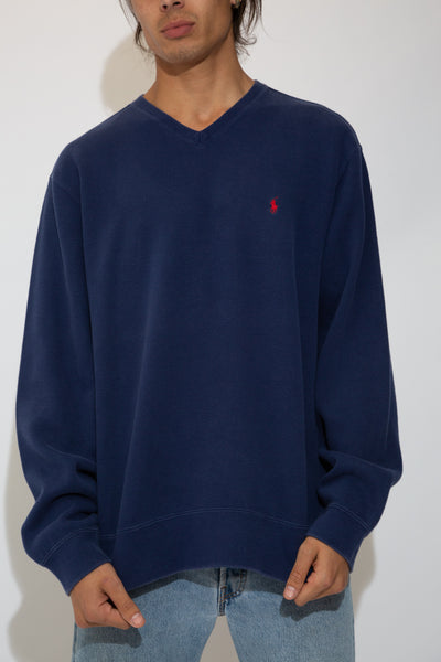 Model is wearing a v neck sweater that is navy and features the ralph lauren logo on the left chest in red.