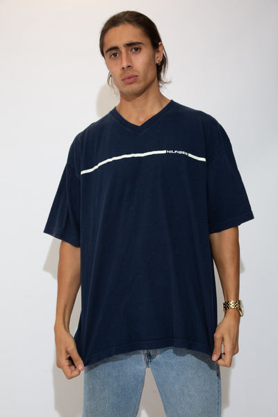 model is wearing a navy v - neck tee made by Tommy Hilfiger, the tee features a white stripe with the words Hilfiger on the left chest