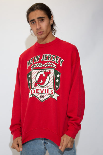 Red in colour with a large green and white New Jersey spell-out across the top and the Devils logo printed below in a coat of arms style. Repping the NHL at the bottom