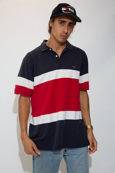 the model is wearing a red, white and navy polo made by nautica.