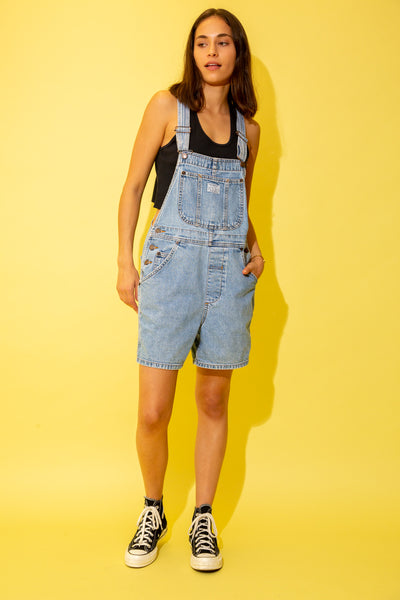 These dungaree shorts are a light-wash blue with light brown stitching, a large front pocket, smaller side pockets and bronze buckles, buttons and domes. Branding on the back, front and on the buttons and domes.