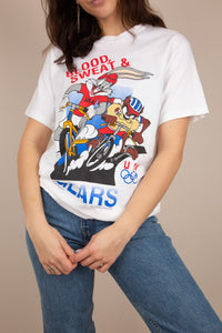 This white tee has a colourful print of Bugs Bunny and Taz racing bicycles for USA on the front. 'Blood, Sweat & Tears' and the Olympics logo are printed in red and blue. Dated 1995, this top is a vintage must-have.