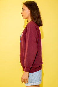 Maroon in colour with a stretched-out crew neck style and a colour print of two ducks on the front.