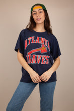 Load image into Gallery viewer, Navy blue single-stitch tee with red and white 'Atlanta Braves' across the front with logo below. Dated 1989. Stretched out neckline adds to loose fit.