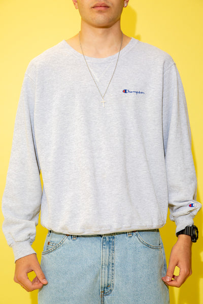 The model is wearing a grey Champion sweater the features the classic Champion script logo on the left side