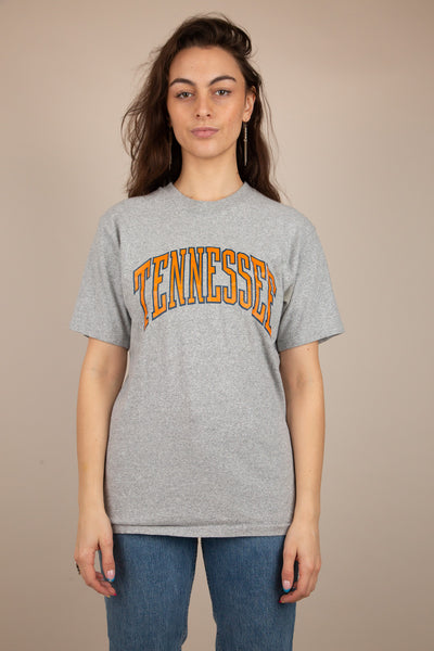 Thick grey tee with orange and navy print of 'Tennessee' across the front. With a ribbed neckline and single-stitching, this tee is a vintage must-have!