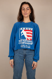 Cornflower blue sweater with a red and white ice hockey print on the front. 1988 National Championships printed below. Cropped to keep it cute, this is a vintage must-have.
