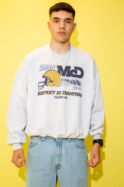 The model is wearing a grey sweater that features a massive spellout on the front