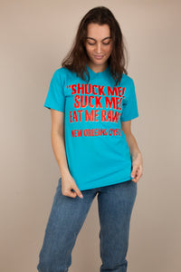 This sky blue top has 'Shuck Me Suck ME Eat Me Raw' printed across in blood orange red. 'New Orleans Oyster' is written at the bottom of this single-stitch tee.