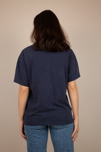 This tee is navy blue with a light blue photo print of John Lennon taken by Yoko Ono Lennon on the front. A stretched out, ribbed neckline adds to the loose fit. Dated 1998.