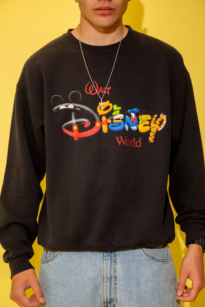 The model is wearing a black sweater that features the Walt Disney logo on the front with the famous characters in the letters.