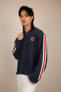 The model is wearing a Tommy Hilfiger Jeans long sleeve shirt. The top features a red lined V neck and white and red piping down the sleeves