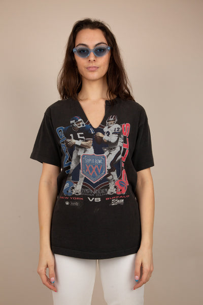 the model is wearing a black tee with cracking on the front of. the print as well as a slit on the front of the and middle of the shirt.