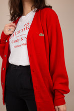Load image into Gallery viewer, the model is wearing a cardigan opened up showing a white tee underneath, the sweater features a small crocodile on the left side. This red knit features 6 buttons.