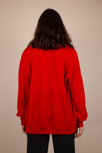 the model is wearing a cardigan opened up showing a white tee underneath, the sweater features a small crocodile on the left side. This red knit features 6 buttons.