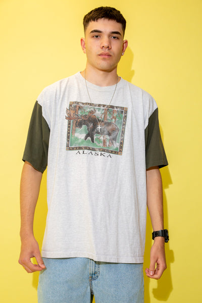 The model is wearing a grey tee that features a massive moose on the front. the tee has green sleeves and is single stitched