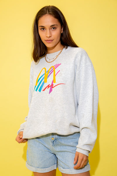 Grey in colour in a baggy, oversized style with the yellow McDonalds logo on the front and some colourful squiggly lines behind it in a 90's retro style.