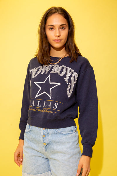 Navy blue in colour with a cropped fit crew neck style. A large silver 'Cowboys' spell-out is printed across the front with the cowboys logo while repping the NFL below. Dated 1996.