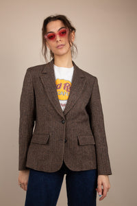 The model is wearing a brown wool blazer, the blazer features two buttons and two pockets either side.