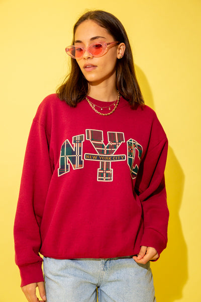 Red in colour with a crew neck style, this sweater has a large NYC spell-out across the front in a tartan pattern. 'New York City' is printed in smaller letters.