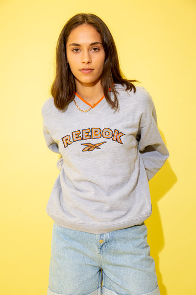 Grey in colour with an orange outlined v-neckline. A large Reebok appliqué is stitched across the front in navy blue and orange with the Reebok logo below.