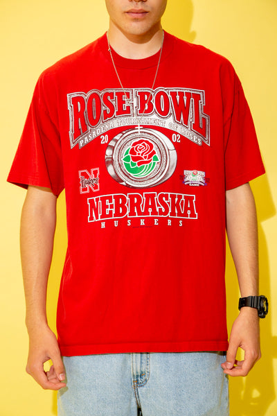 The model is wearing a bright red tee that features the Pasadena rose bowl on the front