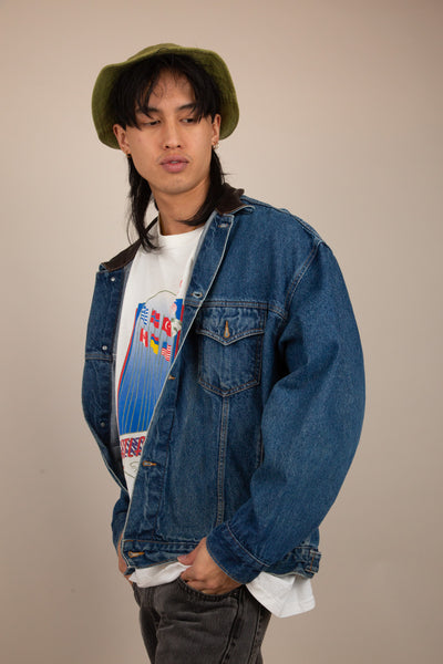 The model is wearing a dark blue denim jacket which features a leather collar as well as having Marlboro fitted buttons coming up the jacket.