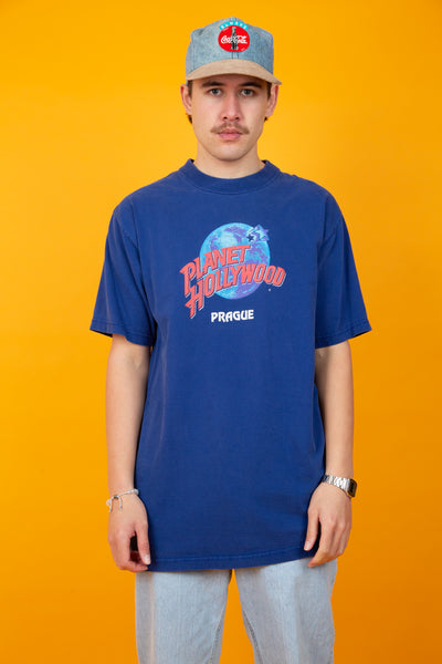 Thick blue cotton tee with a planet hollywood logo printed across the chest of the tee. Small Prague spell out underneath the printed logo.