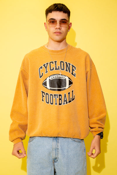 The model is wearing a tan sweater with a massive sports spellout the sweater fits oversized on the model