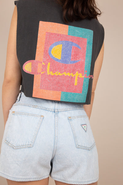 faded black cropped singlet with champion text graphic on left chest and large colourful graphic on back