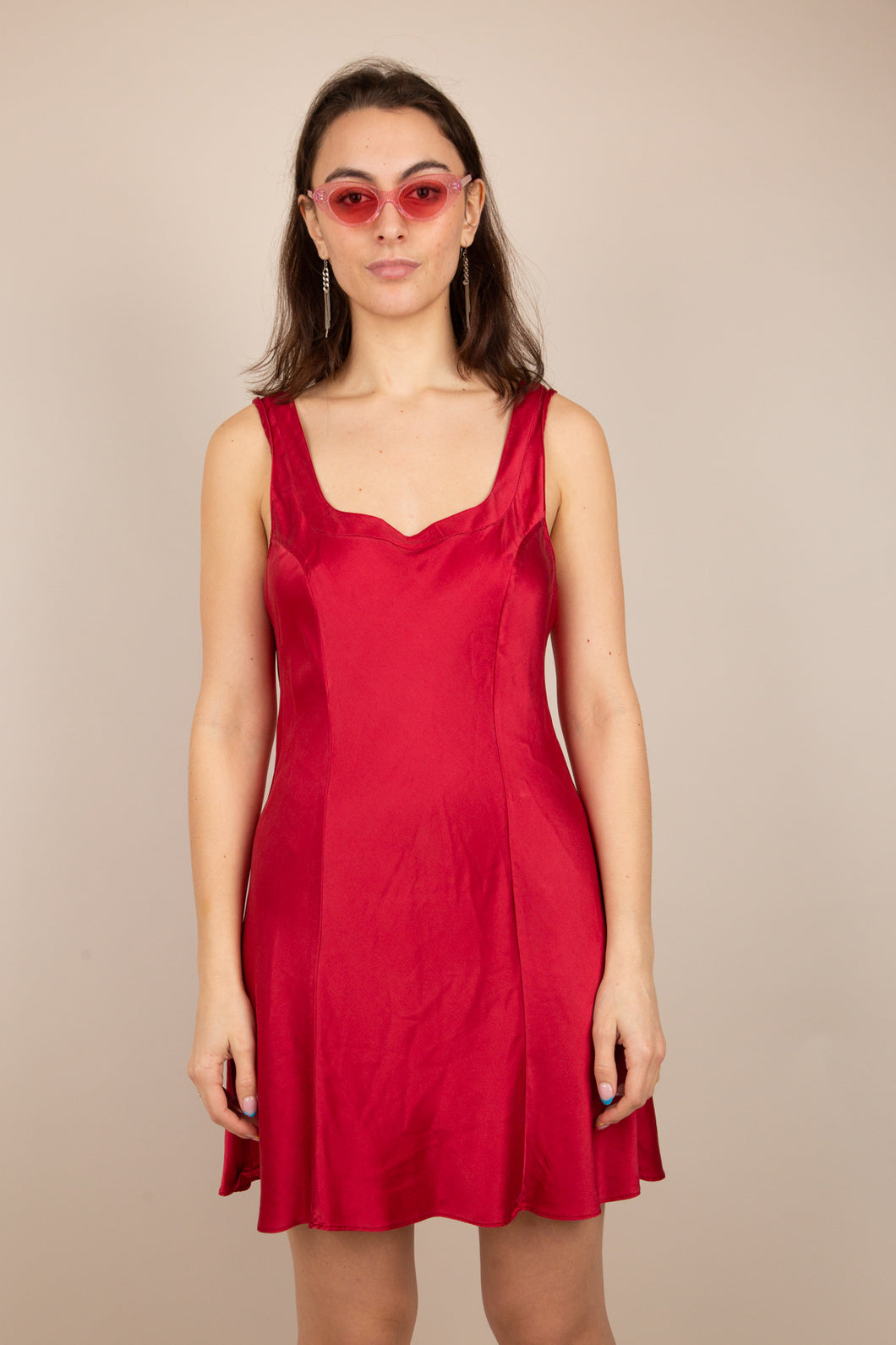 Model is wearing a silk like dress that is mid length. The dress features thick dress straps.