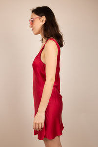 Side profile of the model wearing a red silk like dress