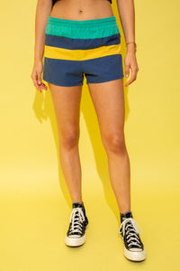 Lightweight cotton shorts with horizontal stripe panels featuring a navy, yellow and turquoise colou-rway. These shorts also feature an elasticated waist and drawstring detail, and they have a thin mesh lining on the inside. Style these shorts with a white Nike crop and some all white AF1's for a sporty, summery look.