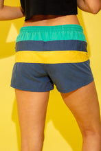 Load image into Gallery viewer, Lightweight cotton shorts with horizontal stripe panels featuring a navy, yellow and turquoise colou-rway. These shorts also feature an elasticated waist and drawstring detail, and they have a thin mesh lining on the inside. Style these shorts with a white Nike crop and some all white AF1's for a sporty, summery look.