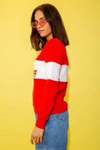 Cute fitted red sweater with a white panel across the middle with a flag graphic and a 'Maine' spell-out. Maine is a State in the North East of the USA that is famous for its jagged, rocky coastline, low, rolling mountains, heavily forested interior, picturesque waterways, and its seafood cuisine.