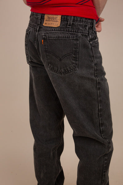 faded and distressed black levi 550 jeans