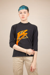 faded black top with 3/4 sleeves and vibrant bugle boy graphic