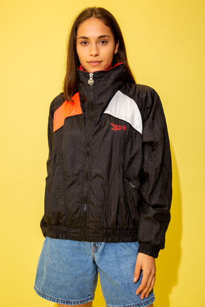 Zip Up jacket with rain jacket feel. Black, with a pink foldable collar, right shoulder, patched back and Reebok branding on the left chest. With a white patched shoulder and back and easy zip-up pockets.