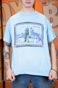 the model wears a blue tee with a wolf graphic on the front