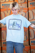 Load image into Gallery viewer, the model wears a blue tee with a wolf graphic on the front