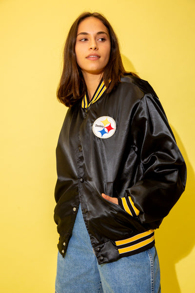Black with a silky exterior and a yellow, black and white striped collar, waistline and arms, this bomber-style jacket has dome closure, pockets and the Steelers logo on the left chest.