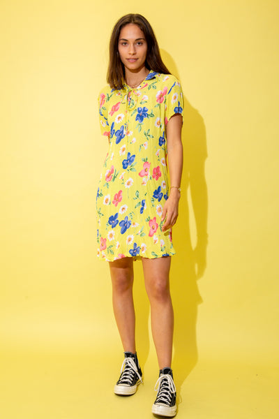 Yellow in colour, in a mini dress style and patterned in pink, blue and white flowers, this dress has a lace-up neckline, triangular collar and flowy skirt.