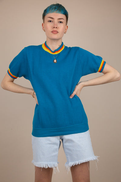 blue short-sleeved sweater with bright orange and yellow contrast stripe detailing on sleeves and neckline