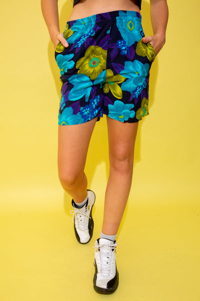 Dark purple shorts in a soft material with a large blue and green flower pattern. With their flowy design and elasticated waistline, these shorts are perfect for the summer holidays