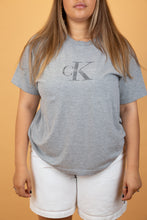 Load image into Gallery viewer, This Calvin Klein single-stitch tee is a soft grey colour with a printed 'CK' graphic and spell out on the chest. This classic design is highly sought after and is an essential for any wardrobe!