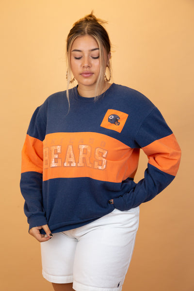 This sweater is striped in navy blue and orange with a large 'Chicago Bears' spellout across the front and branding on the left chest. Oversized, baggy fit.