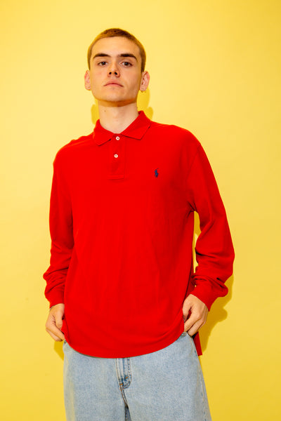 Red in colour with a ribbed material feel, navy Nautica branding on the left chest and white shell-like buttons.