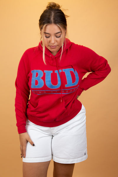 Red hoodie with a large blue spell-out of 'Bud King of the Beers' in blue across the front, Dated 1988 below. Finished off with a hood, drawstrings and a kangaroo-pouch style pocket.