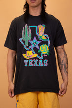 Load image into Gallery viewer, model is wearing a black tee that features a massive neon depiction of the state of Texas