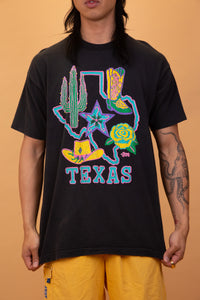 model is wearing a black tee that features a massive neon depiction of the state of Texas